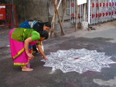 Women drawing an intricate kolam at Mylapore